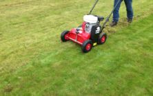 Scarifying a moss infested lawn before over-seeding and applying fertiliser.